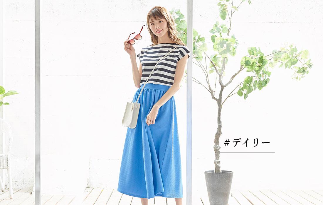 ブルーのエンボスフレアギャザースカートを履いた女性