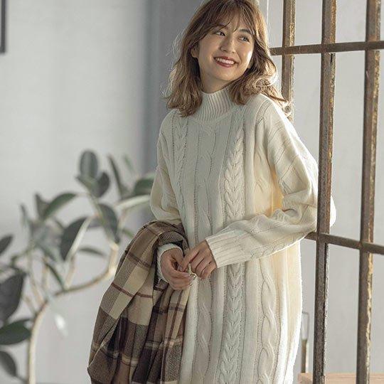 アイボリーのざっくりケーブル編みニットワンピースを着た女性
