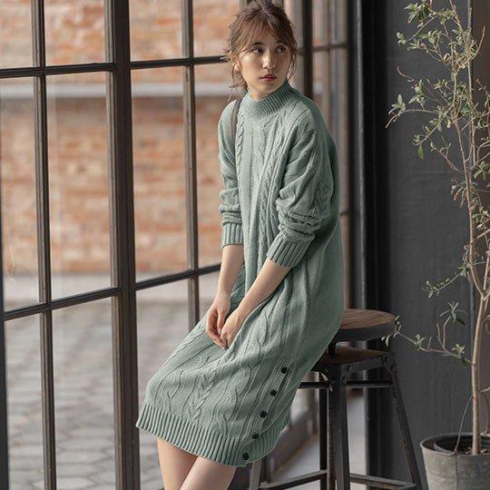 ミントのざっくりケーブル編みニットワンピースを着た女性