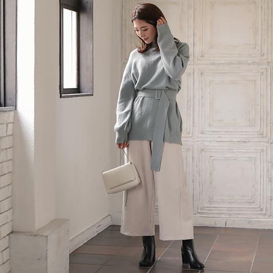 グレーブルーのウエストベルト付きニットトップスを着た女性