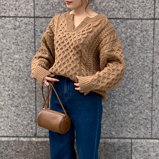 キャメルのローゲージバンドンキーネックニットトップスを着た女性