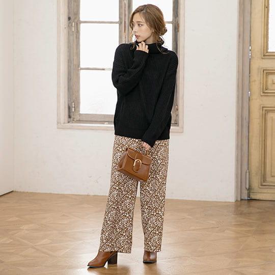 ブラックカラーのざっくり編みタートルを着た女性
