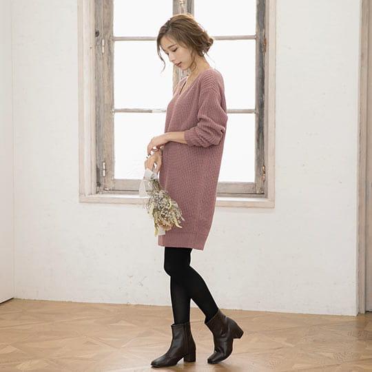 スモーキーピンクカラーのざっくり編みニットワンピースを着た女性
