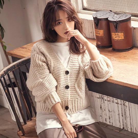 アイボリーのざっくりケーブル編みニットカーディガンを着た女性
