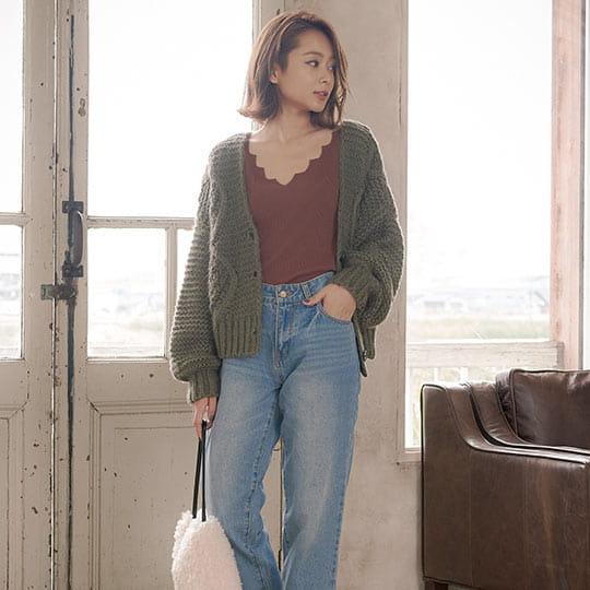 グレーのざっくりケーブル編みニットカーディガンを着た女性