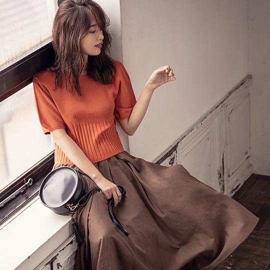 ダークオレンジカラーのニットを着た女性