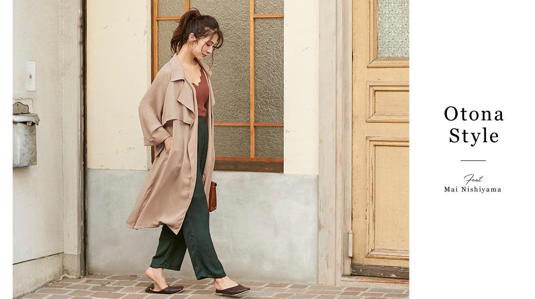 ベージュのジョーゼットトレンチコートとモスグリーンのビンテージサテンパンツを着た西山真以さん
