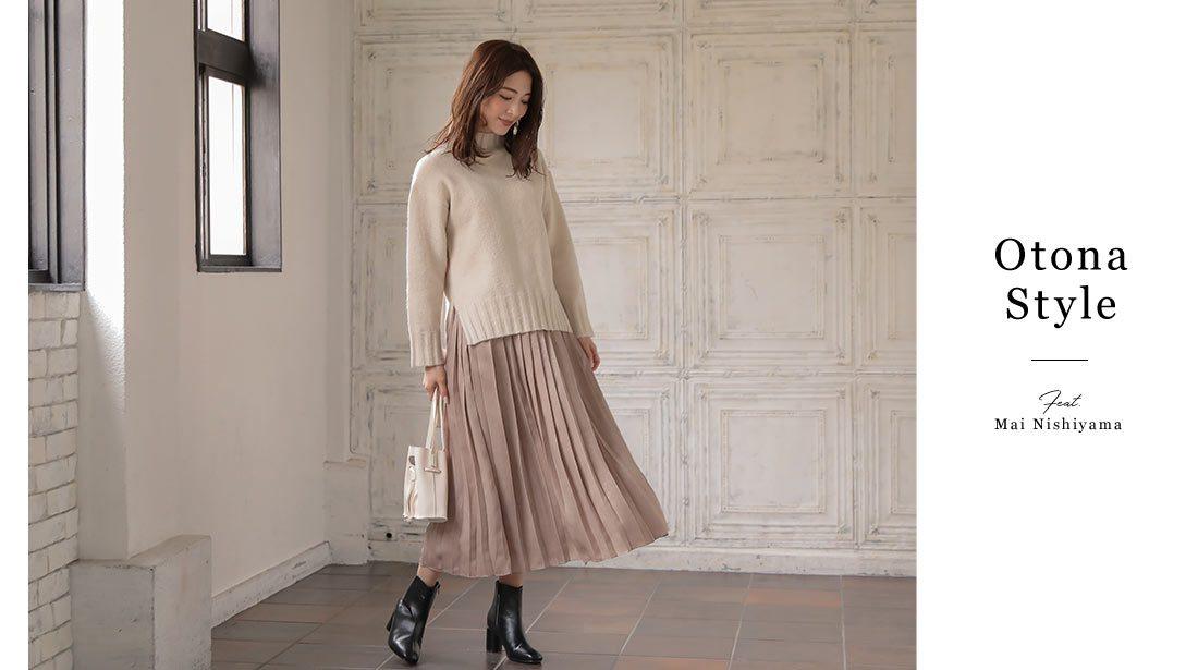 アイボリーのタートルニットとピンクベージュのプリーツスカートを着た西山真以さん