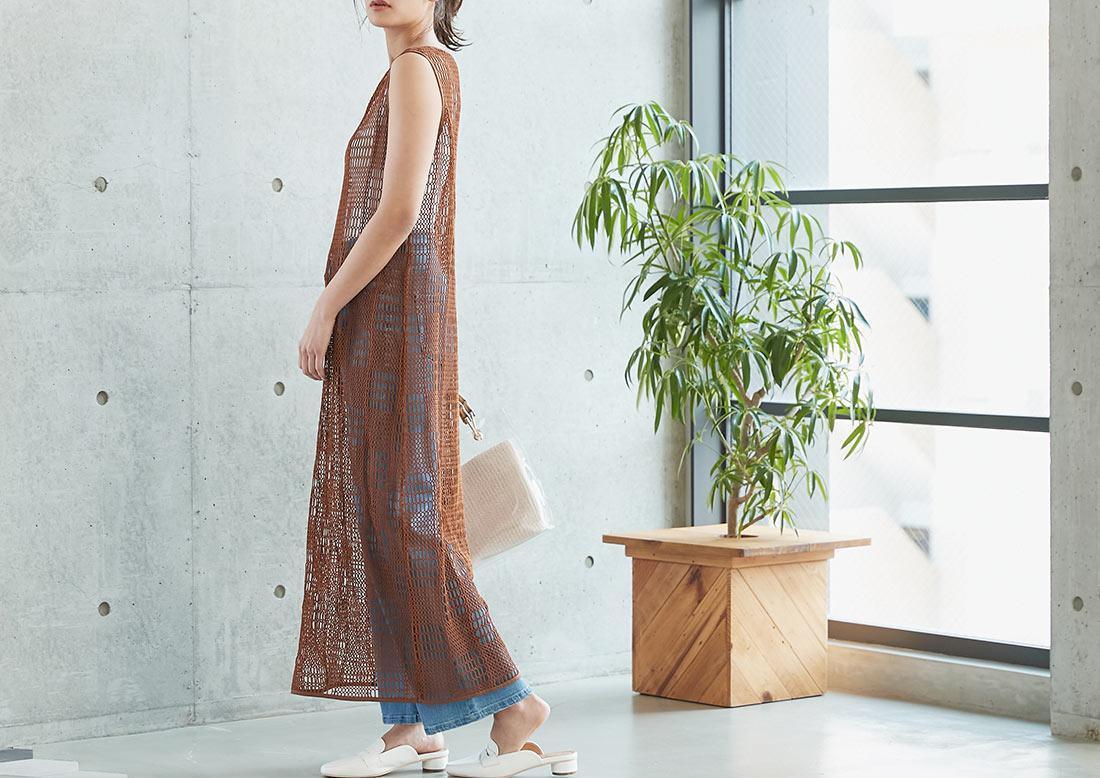 透かしデザインノースリーブワンピースを着た女性