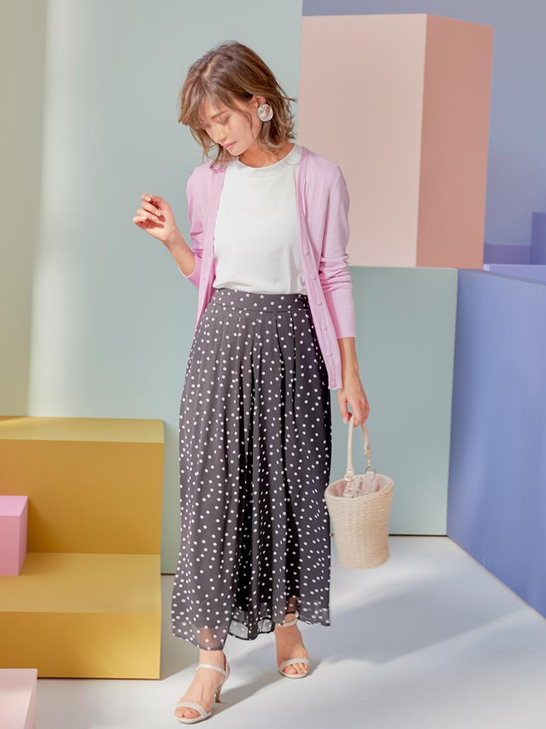 ピンクのカーディガンとドットのスカンツを着た女性
