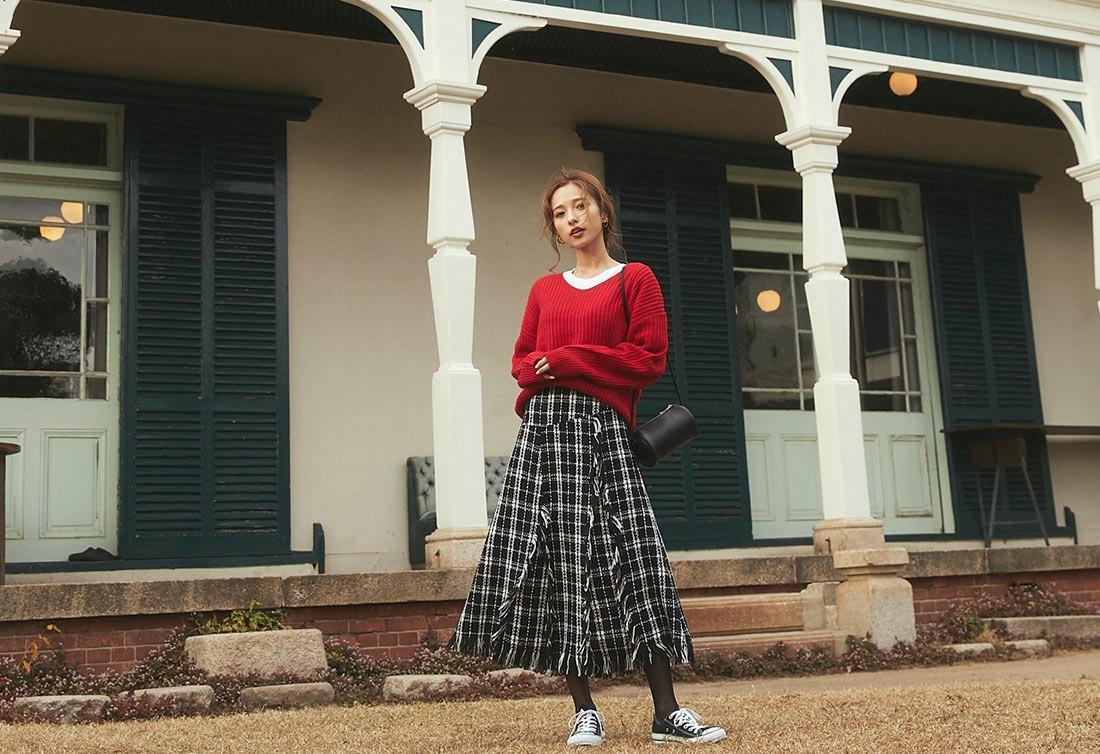 赤のニットとチェックのスカートを着た女性