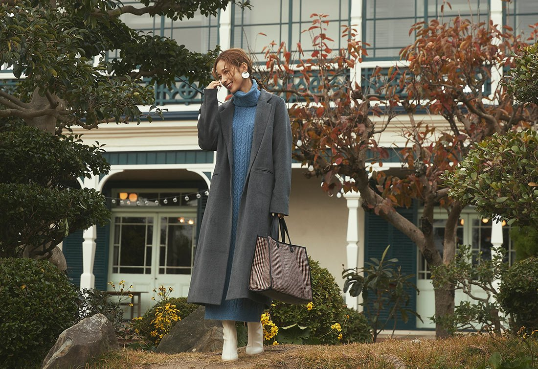 チャコールグレーのチェスターコートを着た女性