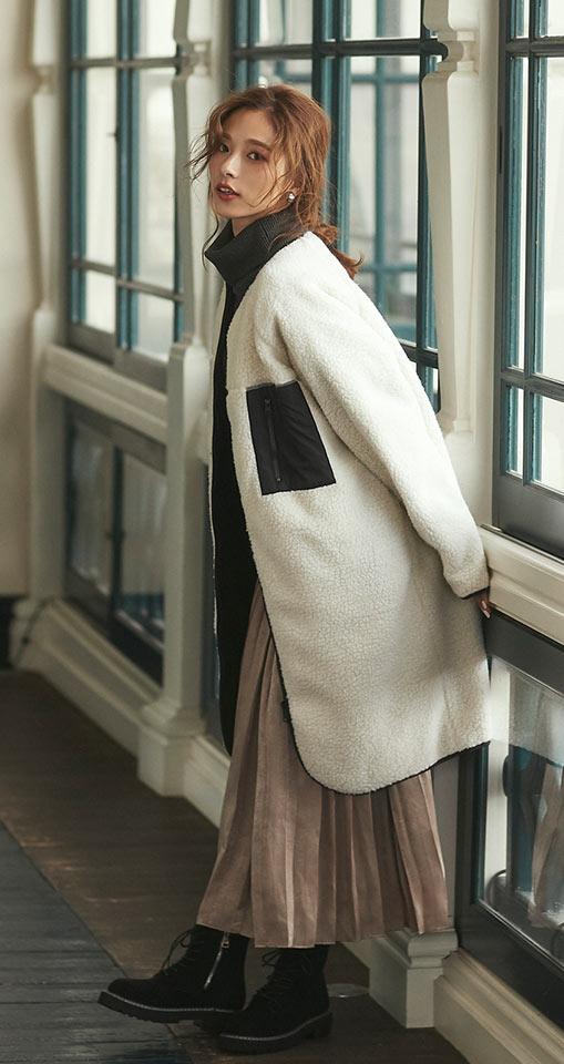 アイボリーのボアブルゾンを着た女性