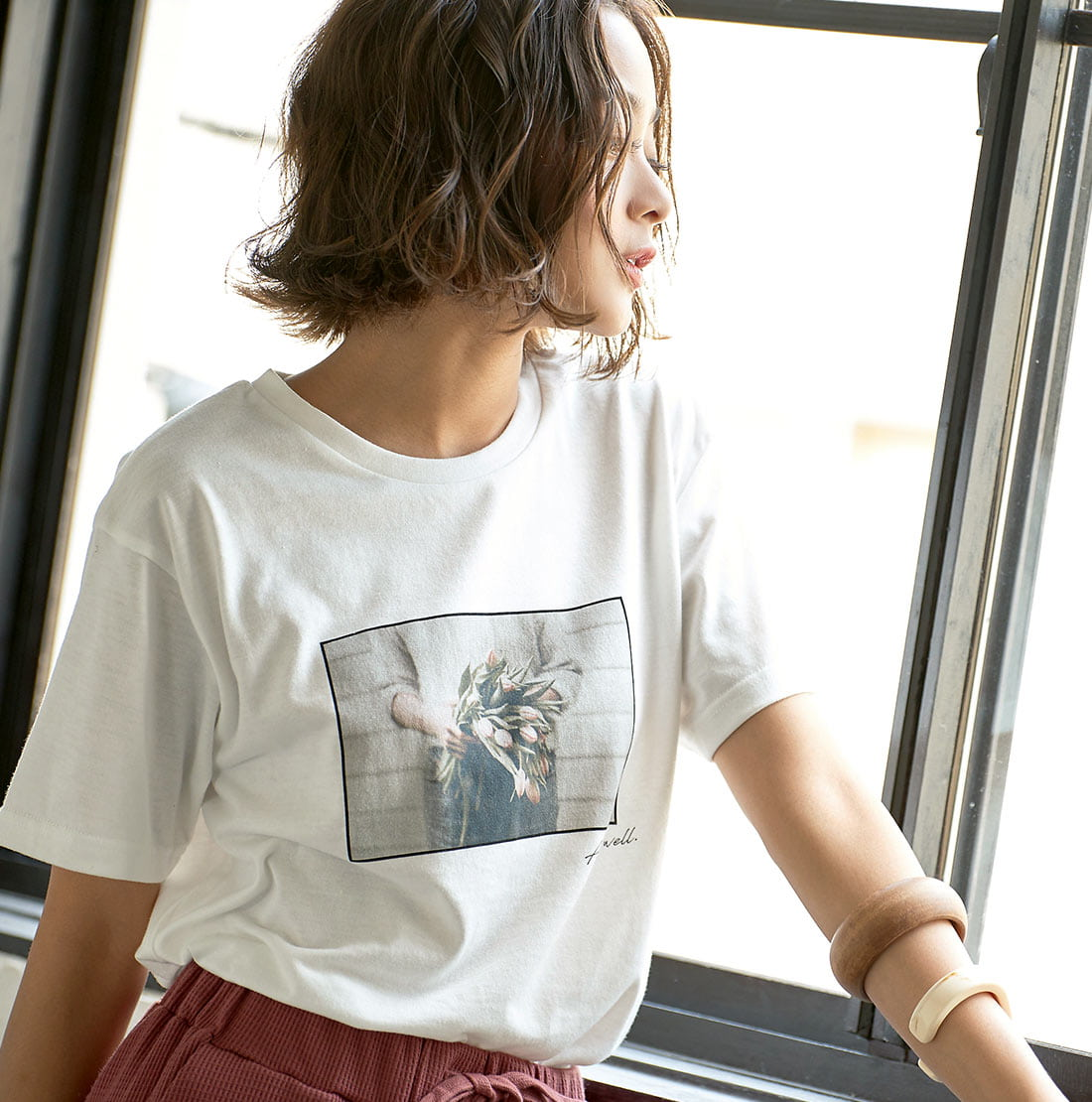 オフホワイトのフォトプリントTシャツを着た女性